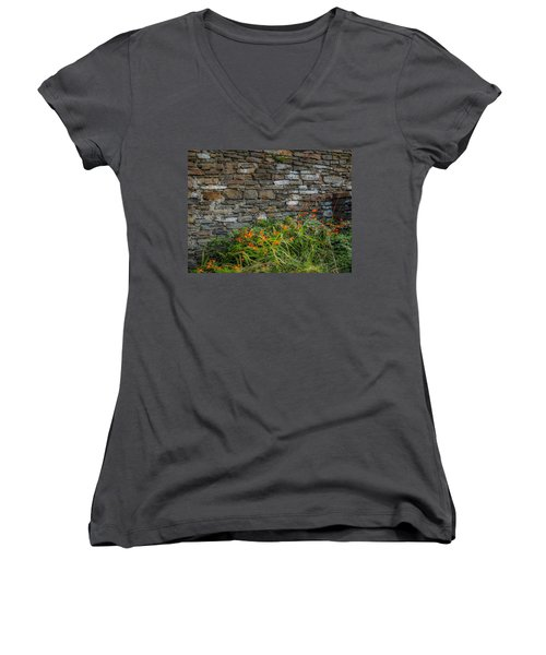 Orange Wildflowers Against Stone Wall Women's V-Neck