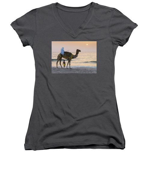 Little Boy Stares In Amazement At A Camel Riding On Marina Beach In Dubai, United Arab Emirates -  Women's V-Neck