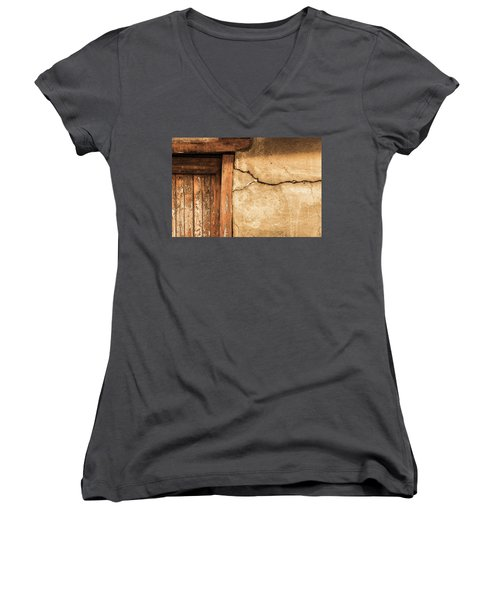 Women's V-Neck T-Shirt (Junior Cut) featuring the photograph Cracked Lime Stone Wall And Detail Of An Old Wooden Door by Semmick Photo
