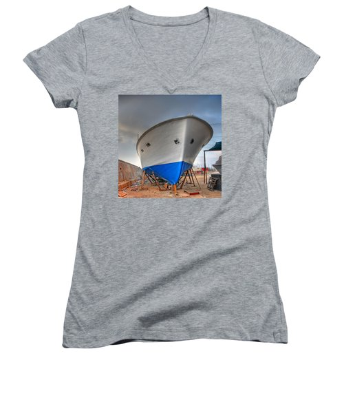 Women's V-Neck T-Shirt (Junior Cut) featuring the photograph a resting boat in Jaffa port by Ron Shoshani