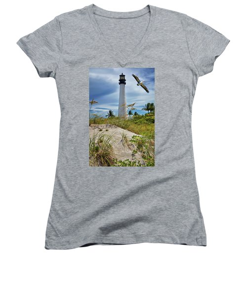 Pelican Flying Over Cape Florida Lighthouse Women's V-Neck T-Shirt (Junior Cut) by Justin Kelefas