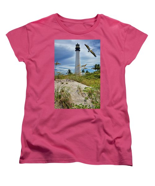 Pelican Flying Over Cape Florida Lighthouse Women's T-Shirt (Standard Cut) by Justin Kelefas