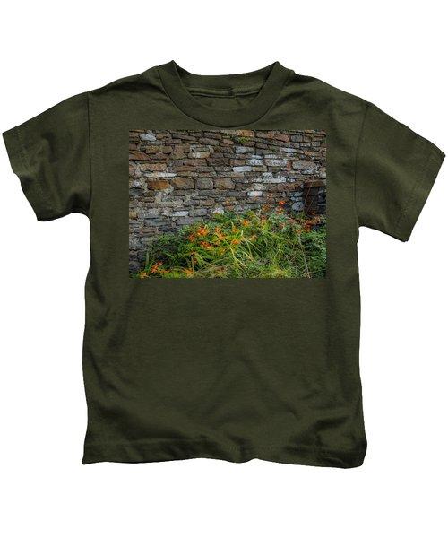 Orange Wildflowers Against Stone Wall Kids T-Shirt