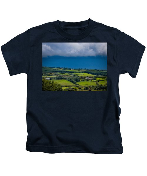 Kids T-Shirt featuring the photograph Clouds Over Shimmering Green Irish Countryside by James Truett