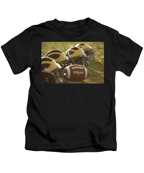 Helmets And A Football On The Field At Dawn Kids T-Shirt