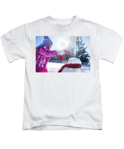 A Young Girl Building A Snowman Kids T-Shirt