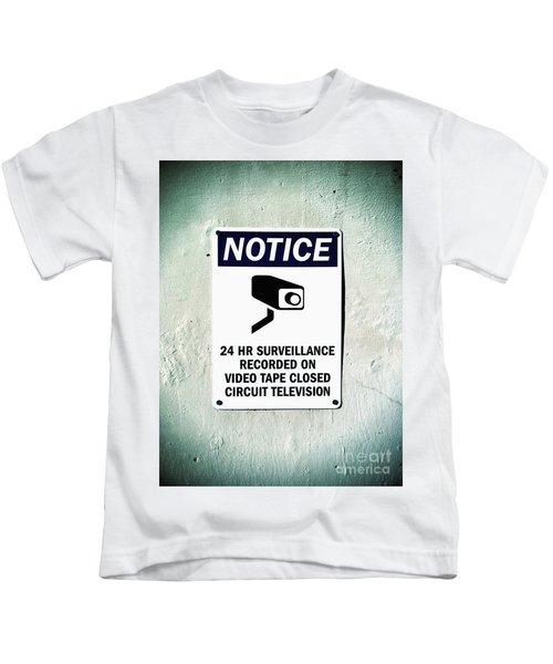 Surveillance Sign On Concrete Wall Kids T-Shirt