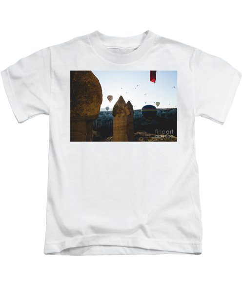 hot air balloons for tourists flying over rock formations at sunrise in the valley of Cappadocia. Kids T-Shirt