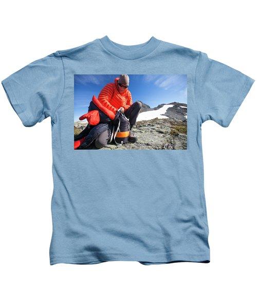 A Backpacker Stuffs His Sleeping Bag Kids T-Shirt