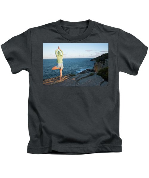 Yoga On Rocky Outcrop Above Ocean Kids T-Shirt