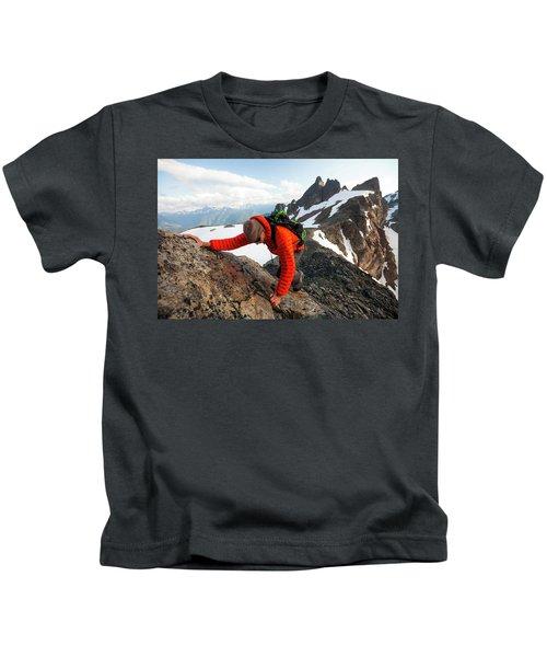 A Climber Scrambles Up A Rocky Mountain Kids T-Shirt