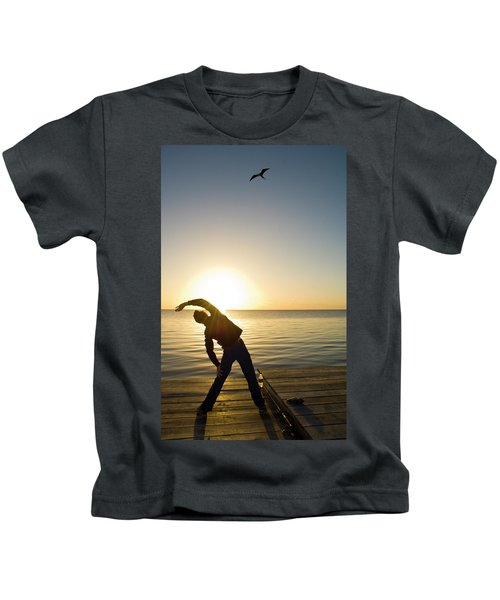 A Person Practices Yoga At The Waters Kids T-Shirt