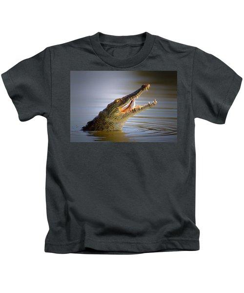 Nile Crocodile Swollowing Fish Kids T-Shirt by Johan Swanepoel