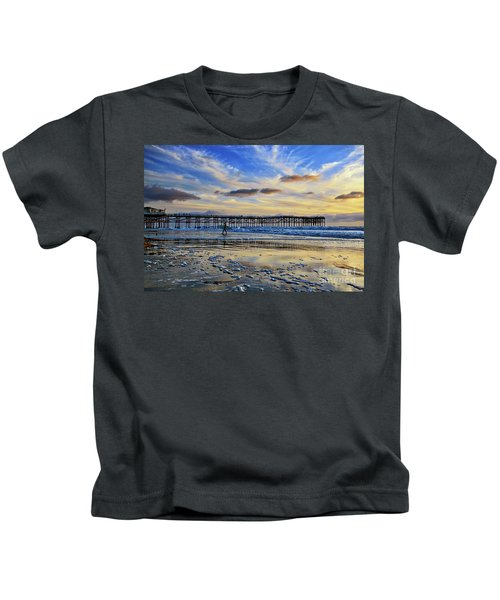 A Surfer Heads Home Under A Cloudy Sunset At Crystal Pier Kids T-Shirt