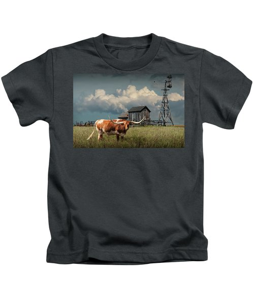 Longhorn Steer In A Prairie Pasture By Windmill And Old Gray Wooden Barn Kids T-Shirt