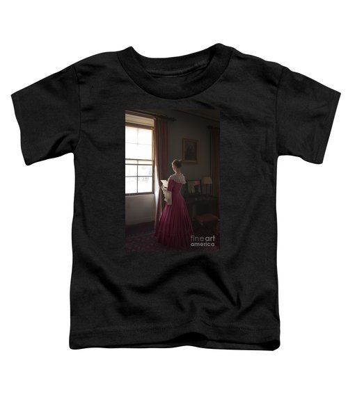 woman reading a letter by the window wearing a pink Georgian dre Toddler T-Shirt