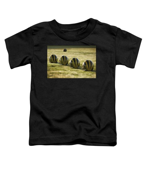 Helmets On Dew-covered Field At Dawn Toddler T-Shirt