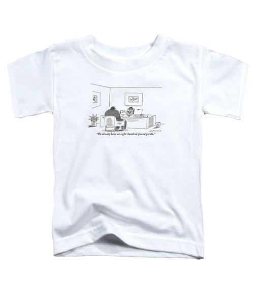 A Woman Behind A Desk Bearing A Sign Saying Toddler T-Shirt