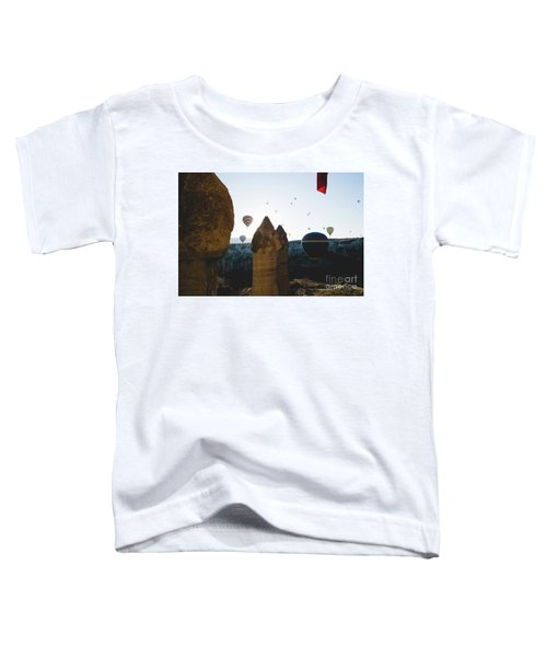 hot air balloons for tourists flying over rock formations at sunrise in the valley of Cappadocia. Toddler T-Shirt