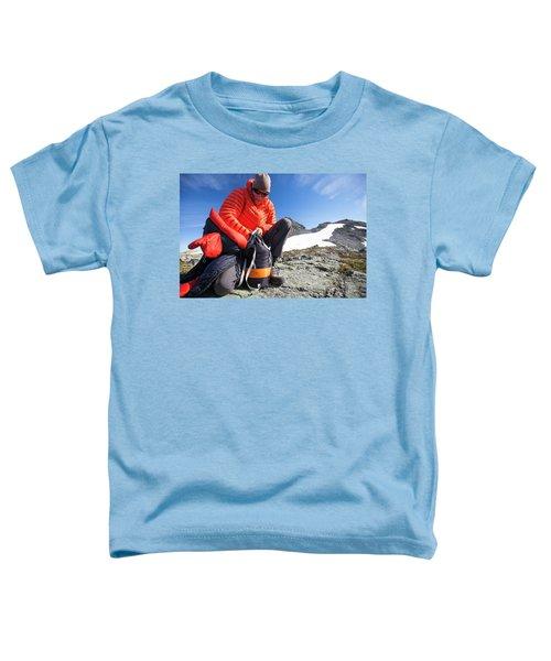 A Backpacker Stuffs His Sleeping Bag Toddler T-Shirt