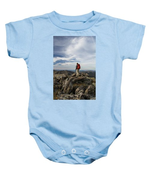 A Backpacker Stands Atop A Dramatic Baby Onesie