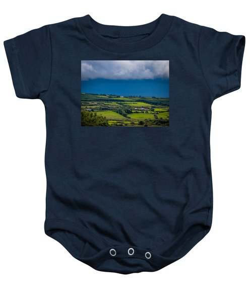 Baby Onesie featuring the photograph Clouds Over Shimmering Green Irish Countryside by James Truett
