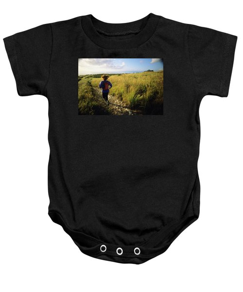 A Young Woman Runs Along A Trail Baby Onesie