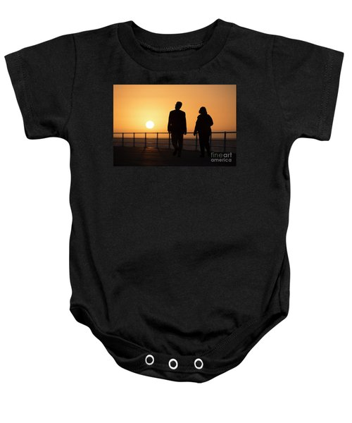 A Couple In Silhouette Walking Into The Sunset Baby Onesie