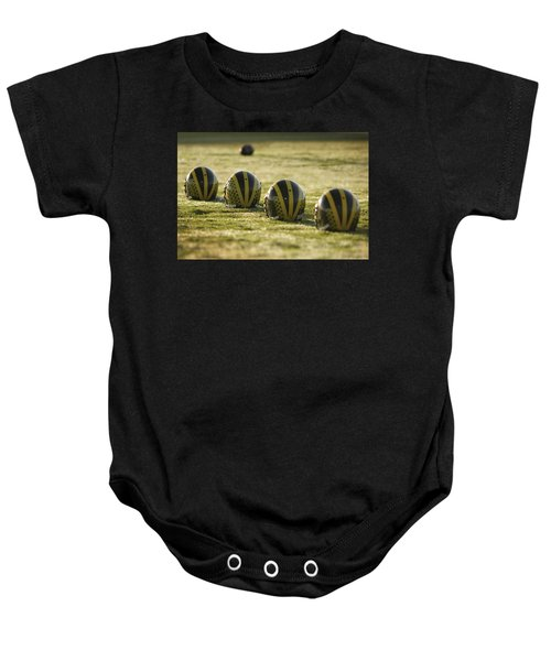 Helmets On Dew-covered Field At Dawn Baby Onesie