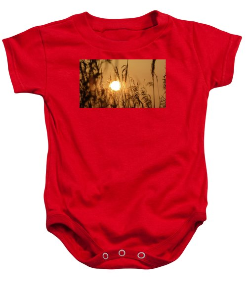 View Of Sun Setting Behind Long Grass B Baby Onesie