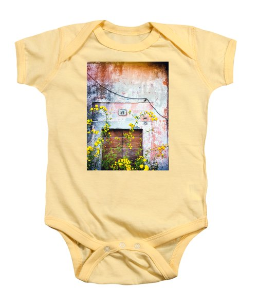 Baby Onesie featuring the photograph Yellow Flowers And Decayed Wall by Silvia Ganora
