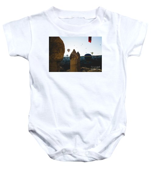hot air balloons for tourists flying over rock formations at sunrise in the valley of Cappadocia. Baby Onesie