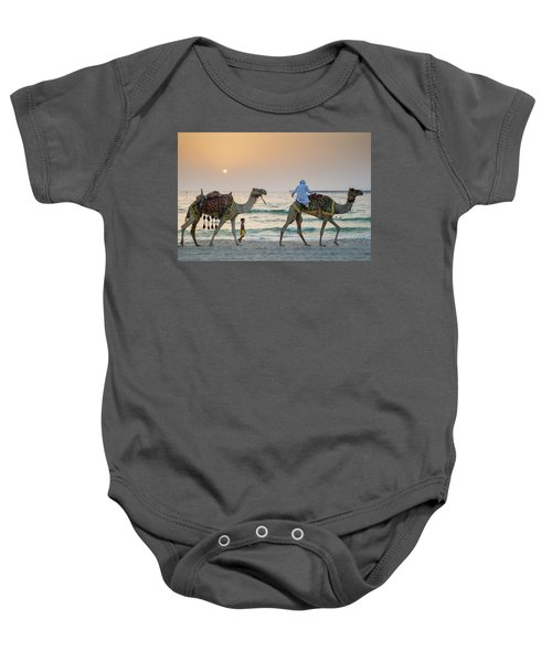 A Little Boy Stares In Amazement At A Camel Riding On Marina Beach In Dubai, United Arab Emirates Baby Onesie