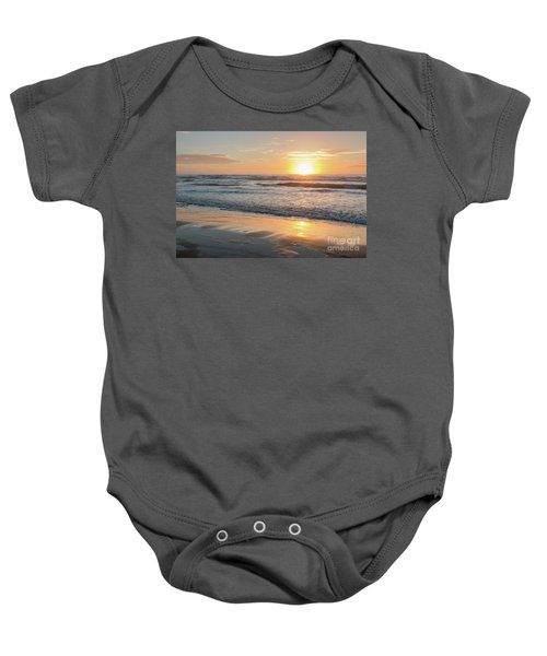 Rising Sun Reflecting On Wet Sand With Calm Ocean Waves In The B Baby Onesie