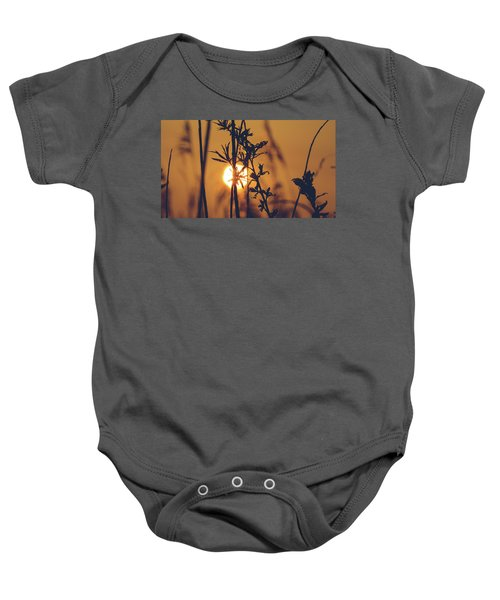 View Of Sun Setting Behind Long Grass D Baby Onesie