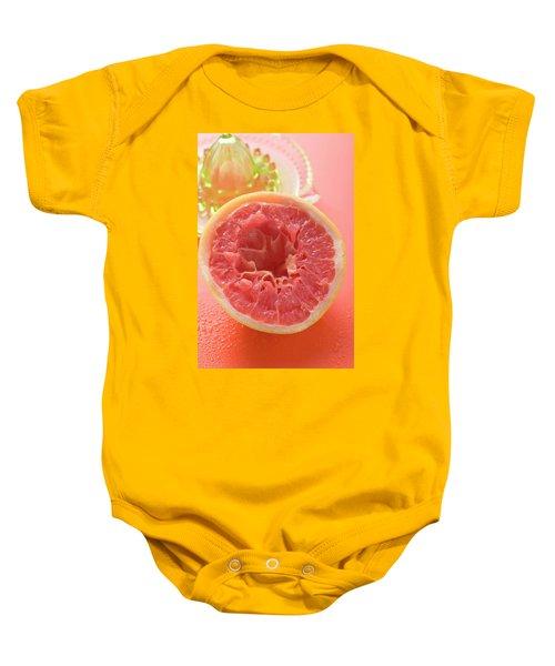 Squeezed Pink Grapefruit In Front Of Citrus Squeezer Baby Onesie