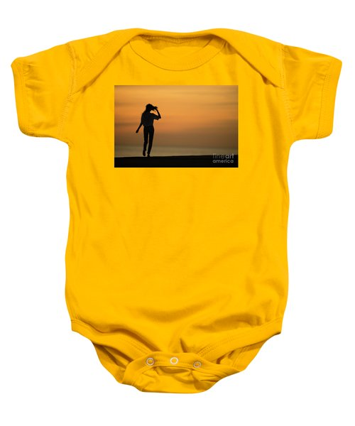 A Slim Woman Walking At Sunset Baby Onesie