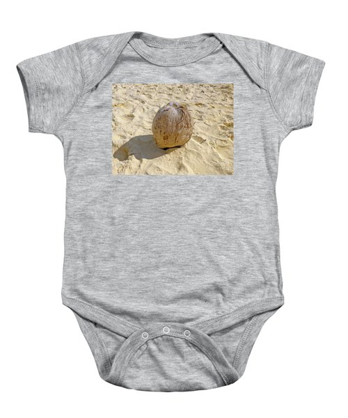 Baby Onesie featuring the photograph Coconut In The Sand by Francesca Mackenney