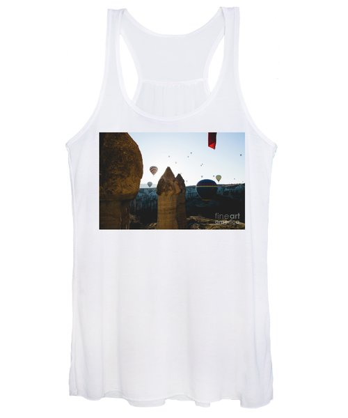 hot air balloons for tourists flying over rock formations at sunrise in the valley of Cappadocia. Women's Tank Top