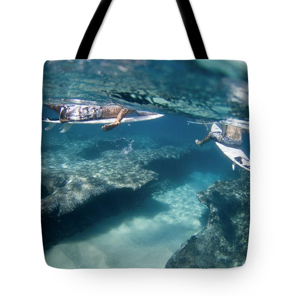 Surfers Over Reef. Tote Bag by Sean Davey