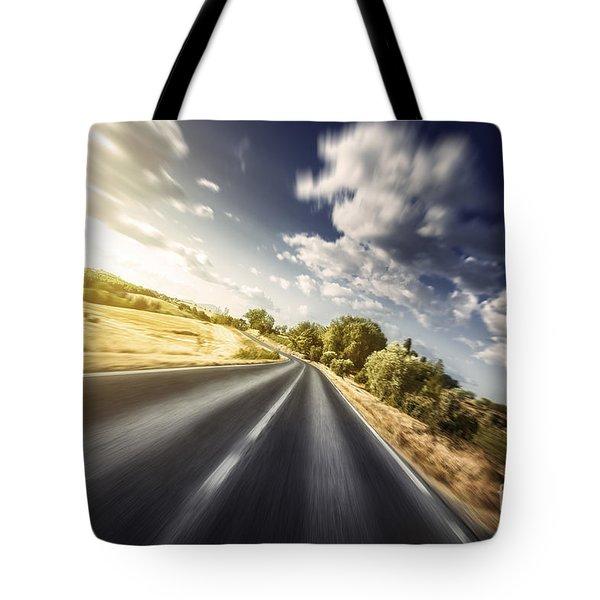 Asphalt Road In Field Against Moody Tote Bag by Evgeny Kuklev