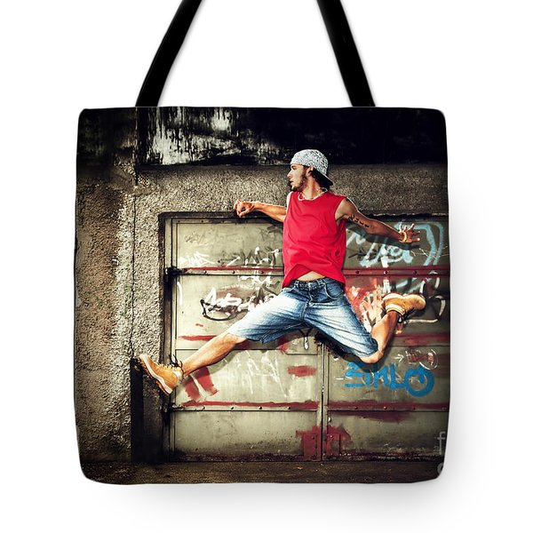 Young Man Jumping On Grunge Wall Tote Bag by Michal Bednarek