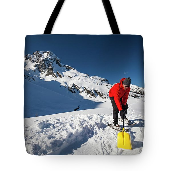 A Climber Shovels Snow In Order To Make Tote Bag