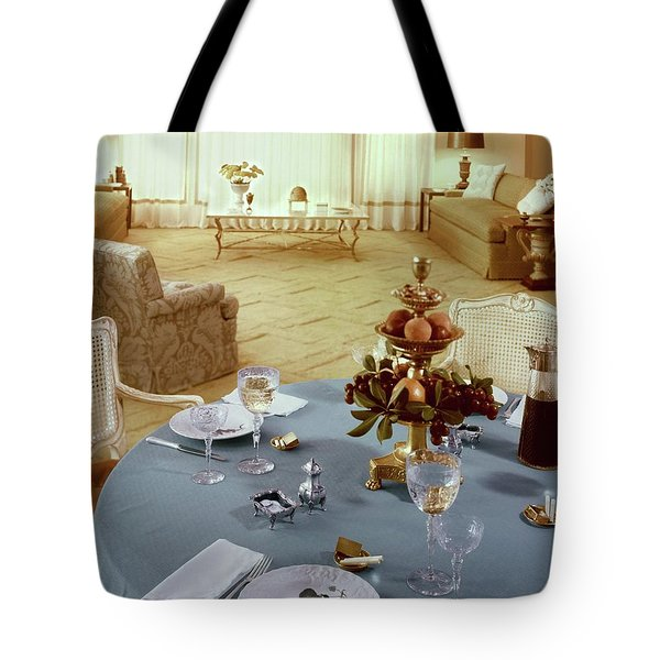 A Dining Room With A Blue Tablecloth And Ornate Tote Bag