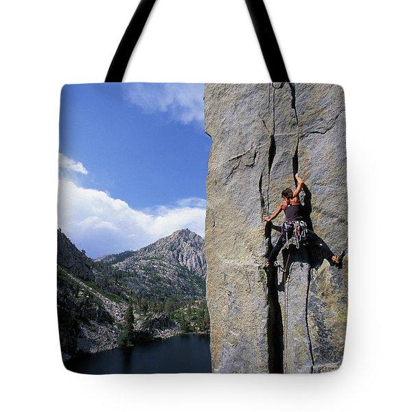 A Female Rock Climber Climbing A Cliff Tote Bag