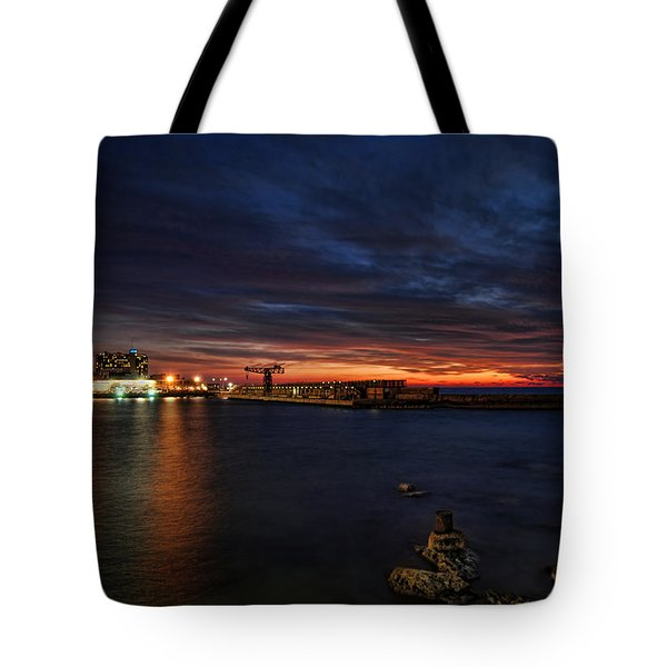 Tote Bag featuring the photograph a flaming sunset at Tel Aviv port by Ron Shoshani