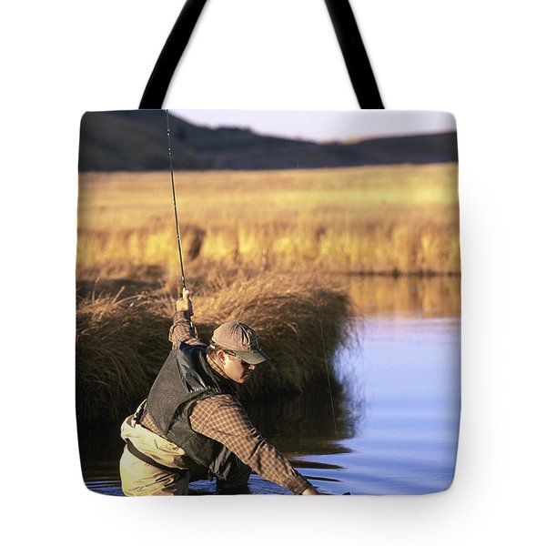 A Fly-fisherman Lands A Trout Tote Bag
