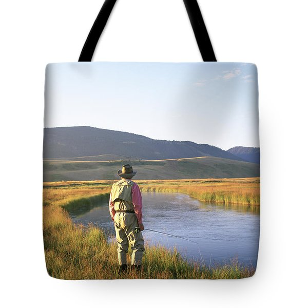 A Fly-fisherman Stands Alongside Tote Bag