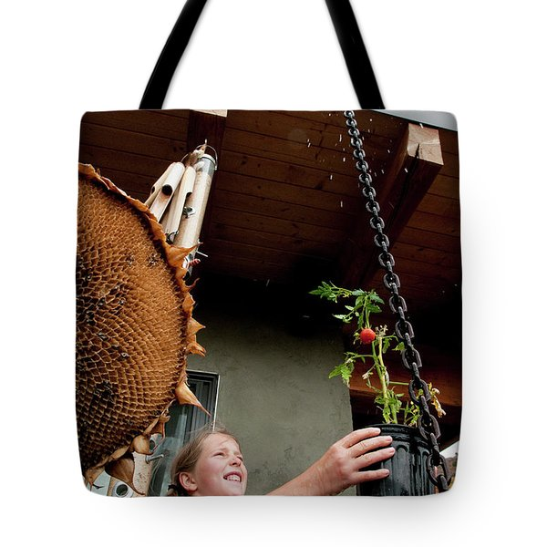 A Girl Smiles As She Waters A Tomato Tote Bag