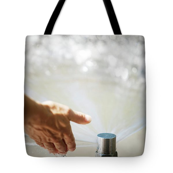 A Hand In A Playground Sprinkler Tote Bag